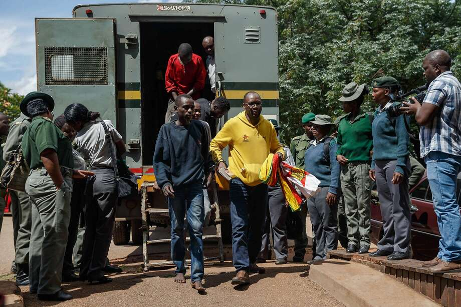 Pastor Evan Mawarire (right), who has supported the protests on social media, exits a prison van as he arrives at a Harare court. More than 600 people have been arrested this week. Photo: Jekesai Njikizana / AFP / Getty Images