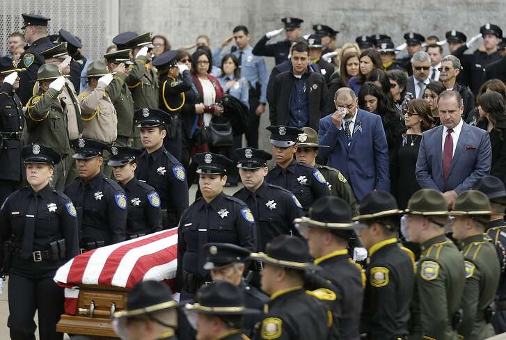 Family members follow the flag draped coffin of Davis Police Officer Natalie Corona before funeral services for Corona at the University of California, Davis, Friday, Jan. 18, 2019, in Davis, Calif.  Corona was was shot and killed Jan. 10, responding to scene of a three-car crash in Davis.  Police say gunman Kevin Douglas Limbaugh, 48, not involved in the crash,  rode up on a bicycle and without warning, opened fire on Corona. (AP Photo/Rich Pedroncelli)