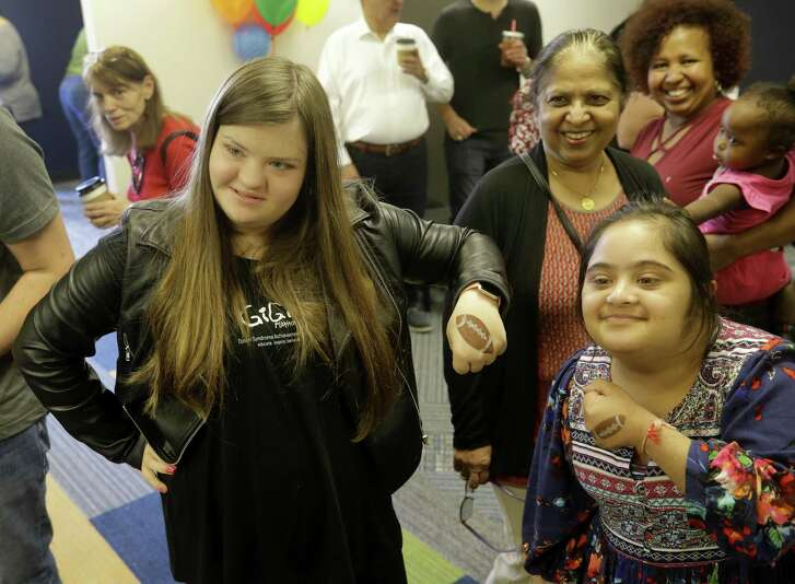 GiGi Gianni, left, poses with Bharti Singh, center, and her daughter, Gunitaa Singh, during the grand opening at GiGi's Playhouse, 1704 Seamist Drive, Saturday, Dec. 1, 2018. The two were showing the footballs painted on their hands. The national organization promotes Down syndrome programs.
