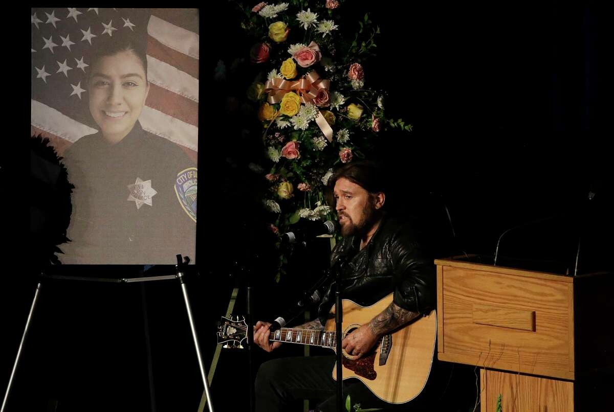 Musician Billy Ray Cyrus performs a song during funeral services for Davis Police Officer Natalie Corona at the University of California, Davis, Friday, Jan. 18, 2019, in Davis, Calif. Corona was was shot and killed Jan. 10, responding to scene of a three-car crash in Davis. Police say gunman Kevin Douglas Limbaugh, 48, not involved in the crash, rode up on a bicycle and without warning, opened fire on Corona.