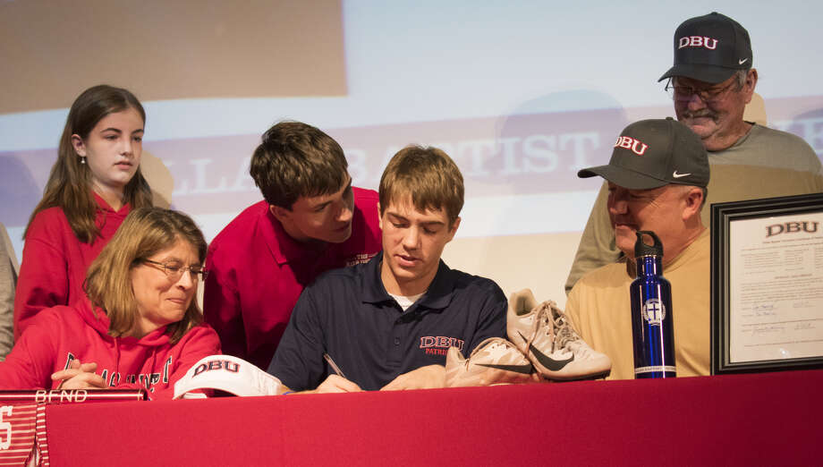 Joe Manning, center, signs his commitment papers to Dallas Baptist University to run track next year. Pictured are from left standing, Sarah Manning, TJ Manning, Tom Taylor, and sitting Brandy Manning, Joe Manning, and Jimmy Manning. Photo: Courtesy Photo