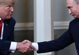 """(FILES) In this file photo taken on July 16, 2018, US President Donald Trump (L) and Russian President Vladimir Putin shake hands ahead a meeting in Helsinki. - Call Donald Trump an egomaniac, call him a showoff. Accuse him of getting kicks from insulting and humiliating people. The thing is, he might just agree. The uniqueness of the 45th US president among world leaders extends to the pride he takes in his brazenly unconventional persona. Trump doesn't just admit to a litany of character flaws and actions that would sink an ordinary politician. He revels in them. """"The show is 'Trump' and it is sold-out performances everywhere. I've had fun doing it and will continue to have fun."""" On January 20, 2019, 72-year-old Trump reaches the halfway mark of his presidency's first term. (Photo by Brendan Smialowski / AFP)BRENDAN SMIALOWSKI/AFP/Getty Images"""