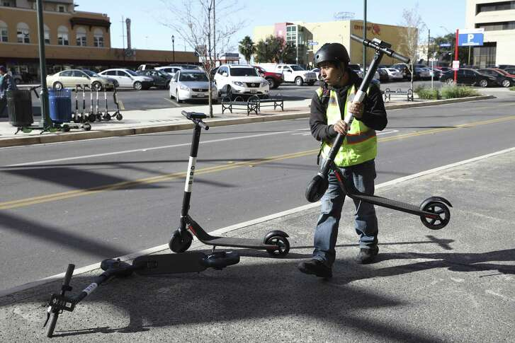 A worker uprights scooters brought down by the wind in downtown San Antonio Dec. 13. Unfortunately, scooters, toppled or otherwise, often congest the city's sidewalks, making it harder on pedestrians, particularly pedestrians with disabilities.