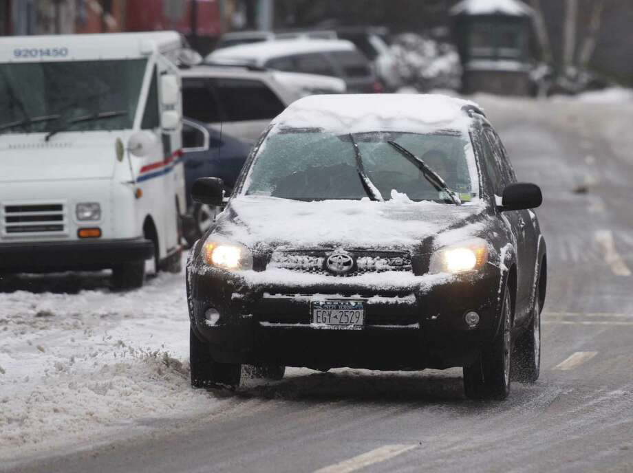 A snow-covered car drives through the slush and ice along Greenwich Avenue in downtown Greenwich, Conn.  Photo: Tyler Sizemore / Tyler Sizemore / Greenwich Time