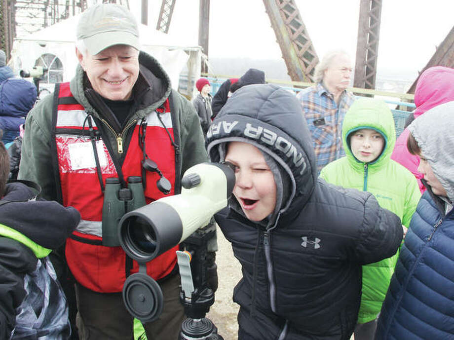 Nathan Horrop, a fifth-grade student at Eastwood Elementary School in East Alton, watches a pair of bald eagles through a spotting scope as volunteer Bob Virag supervises. Several hundred Illinois schoolchildren got a chance to see bald eagles in the wild and close up on the Old Chain of Rocks Bridge as part of its Eagle Days program Friday. The event will be open to the public from 9 a.m. to 3 p.m. Saturday and Sunday, featuring live eagle demonstrations by the World Bird Sanctuary, a chance to view bald eagles in the wild, and other activities. Photo: Scott Cousins | The Telegraph