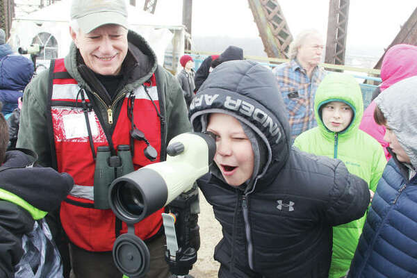 Nathan Horrop, a fifth-grade student at Eastwood Elementary School in East Alton, watches a pair of bald eagles through a spotting scope as volunteer Bob Virag supervises. Several hundred Illinois schoolchildren got a chance to see bald eagles in the wild and close up on the Old Chain of Rocks Bridge as part of its Eagle Days program Friday. The event will be open to the public from 9 a.m. to 3 p.m. Saturday and Sunday, featuring live eagle demonstrations by the World Bird Sanctuary, a chance to view bald eagles in the wild, and other activities.