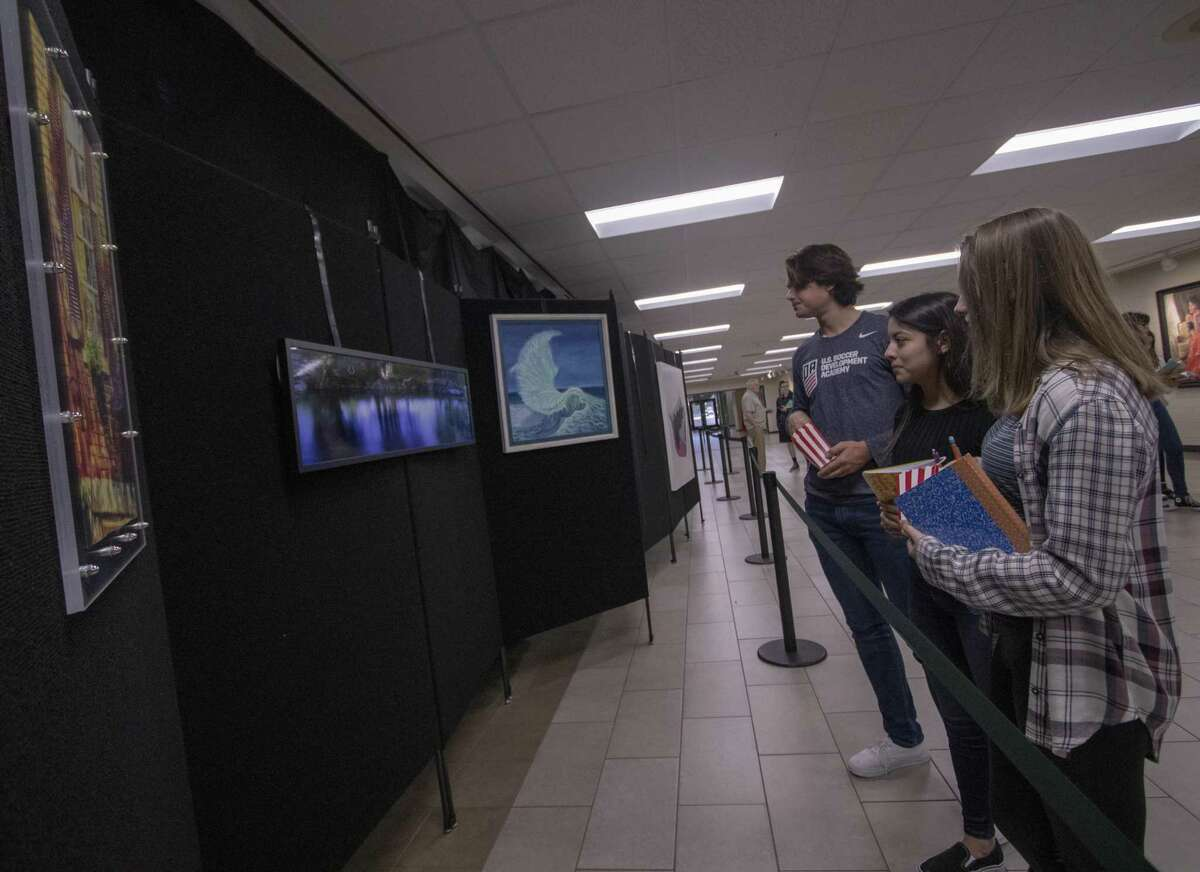 The Woodlands high school students check out art pieces during a reception for The Woodlands High School art trust's 2019 selected pieces Friday, Jan. 18, 2018 at The Woodlands High School.