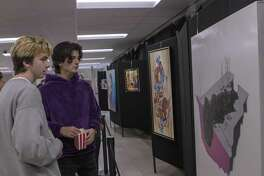 The Woodlands high school juniors Danny Moulis, left, and Kyle Jordan examine art pieces during a reception for The Woodlands High School art trust's 2019 selected pieces Friday, Jan. 18, 2018 at The Woodlands High School.