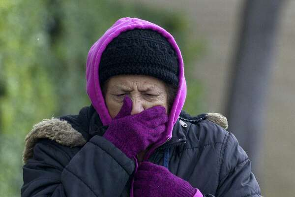 Mary Pursulas, left, covers her mouth from the chilly wind as temperatures dipped into the low 30s resulting in a wintery mix, Tuesday, Nov. 13, 2018.