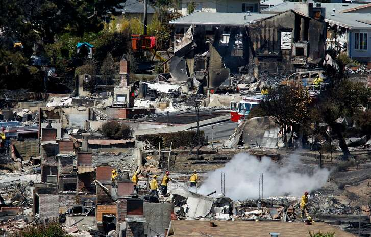 Firefighters spray water on hot spots at a home in San Bruno, Calif. on Friday, Sept. 10, 2010 thaat as destroyed after a massive natural gas pipeline explosion Thursday night.
