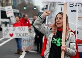 Teacher Chynna Wilson encourages motorists driving past Oakland Technical High School to honk their car horns in support before a march to school district offices in a one day walkout to warn administrators of a possible strike if their contract demands aren't met in Oakland, Calif. on Friday, Jan. 18, 2019.
