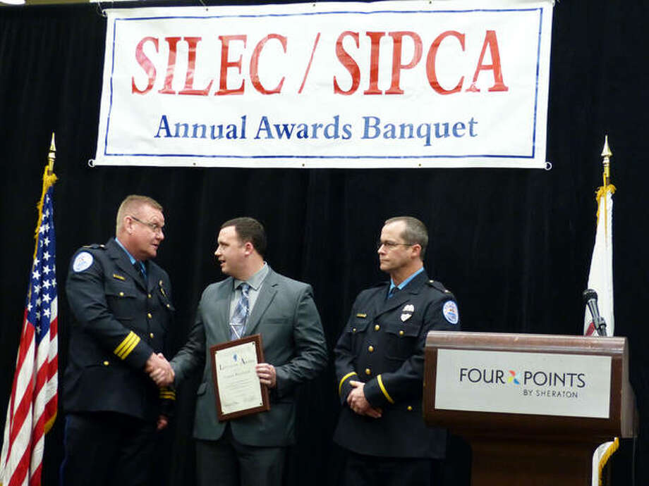 Edwardsville police officer Conor Hoyland, center, shakes hands with Police Chief Jay Keeven, left, alongside Lt. Bryne after the officer was awarded the Life Saving Award at the Southern Illinois Law Enforcement Commission (SILEC) and Southern Illinois Police Chiefs' Association (SIPCA) awards banquet in Fairview Heights Thursday. Photo: Courtesy Of SILEC