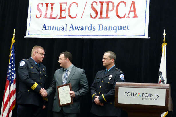 Edwardsville police officer Conor Hoyland, center, shakes hands with Police Chief Jay Keeven, left, alongside Lt. Bryne after the officer was awarded the Life Saving Award at the Southern Illinois Law Enforcement Commission (SILEC) and Southern Illinois Police Chiefs' Association (SIPCA) awards banquet in Fairview Heights Thursday.