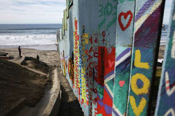 A man stands on the Mexican side of the U.S.-Mexico border barrier at the Pacific Ocean on Jan. 8 in Tijuana, Mexico. A reader reflects on the unfortunate separation of families from the U.S. and Mexico.