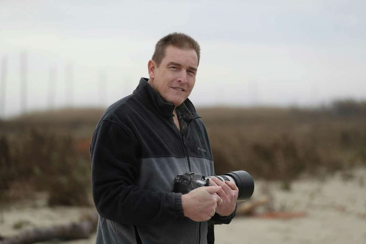 Ron Wooten, an Army Corps of Engineers employee, who moonlights as a wildlife photographer, poses for a photo Friday, Jan. 18, 2019, in Galveston. His photos of coyotes on Galveston's West End, and later tissue samples of dead coyotes that he found, were used to help discover red wolf DNA in the coyote population of southern Texas.