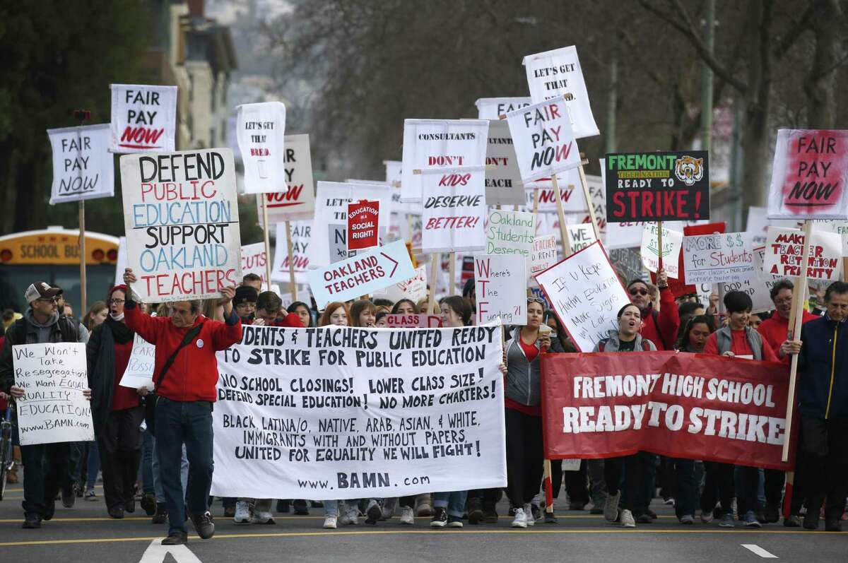 Oakland teachers, students and supporters march to school district headquarters after walking off the job in a contract dispute.