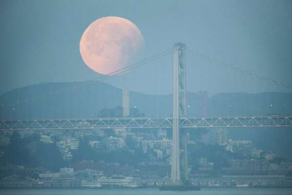 A rare super blue blood moon sets behind the Bay Bridge last January. The lunar eclipse on Sunday is likely to be obscured by clouds.