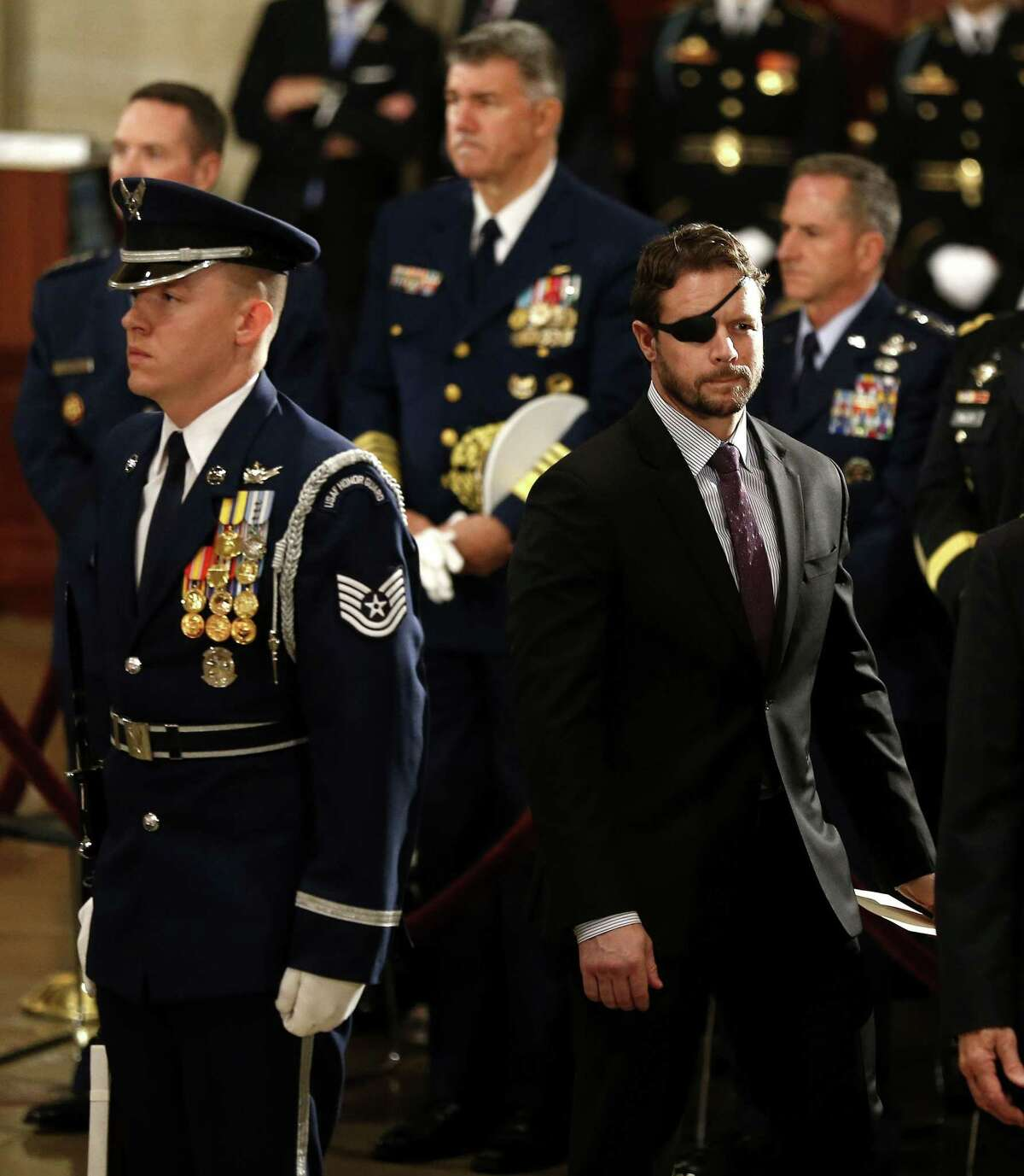 Congressman Dan Crenshaw walks past the casket of President George H.W. Bush during his State Funeral at the United States Capitol Rotunda, Monday, Dec. 3, 2018, in Washington. Bush will lie in state in the Rotunda until Wednesday morning.
