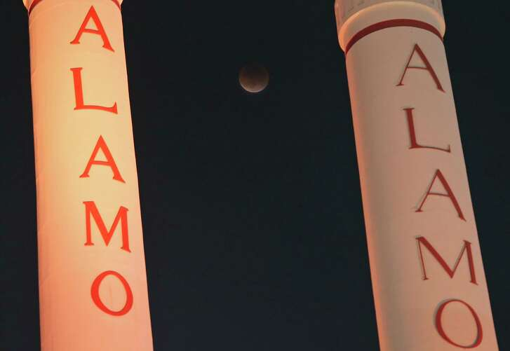 """A view of the """"blood"""" moon eclipse between the smokestacks at the Alamo Quarry Market on Sept. 27, 2015."""