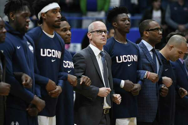 Connecticut head coach Dan Hurley stands with players during the national anthem before an NCAA college basketball game, Sunday, Dec. 2, 2018, in Hartford, Conn. (AP Photo/Jessica Hill)