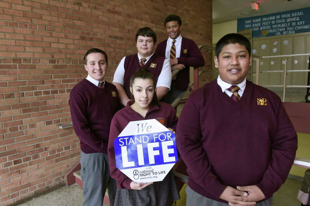 Notre Dame Bishop Gibbons students, foreground left to right, Max Lavoie, Haley Hacker, and Nicholas Mendonca, and background left to right, Ethan Marrone, and Sean Willis, pose for a photo at the school on Wednesday, Jan. 16, 2019, in Schenectady, N.Y. The group of students will be attending the March for Life rally in Washington, D.C. (Paul Buckowski/Times Union)
