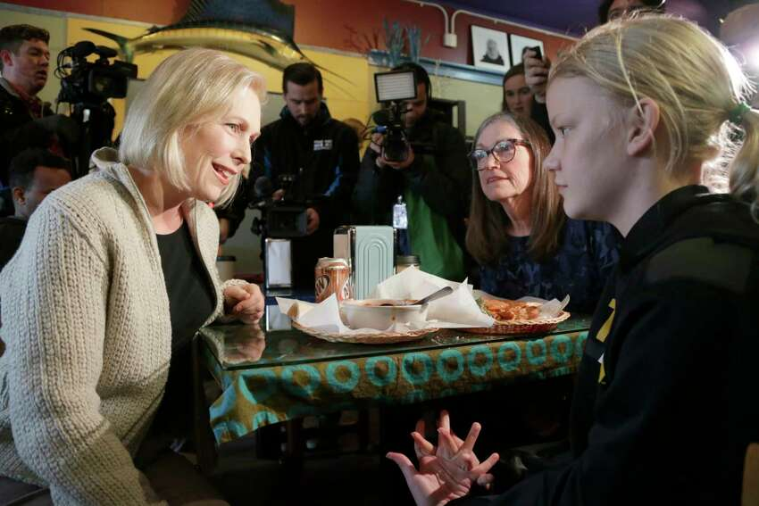 U.S. Sen. Kirsten Gillibrand, D-N.Y., sits down for a chat with Jeanette Hopkins, center, and Chloe McClure, right, at the Pierce Street Coffee Works cafe' in Sioux City, Iowa, Friday, Jan. 18, 2019. Sen. Gillibrand is on a weekend visit to Iowa, after announcing that she is forming an exploratory committee to run for President of the United States in 2020. (AP Photo/Nati Harnik)