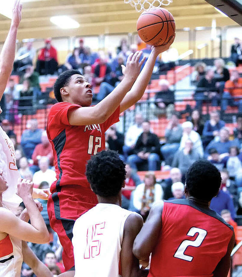 Alton's Josh Rivers (12) made a layup with 16 seconds left to lift Alton past previously unbeaten Trinity of St. Louis 64-62 Friday night in the semifinals of the Chick-fil-A Classic at Belleville East High School. He is shown in action last season against Edwardsville. Photo: Telegraph Photo
