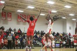 Despite an Atascocita player's try at the block, South Houston's Ian Butler looks for two of his 10 points Friday night.