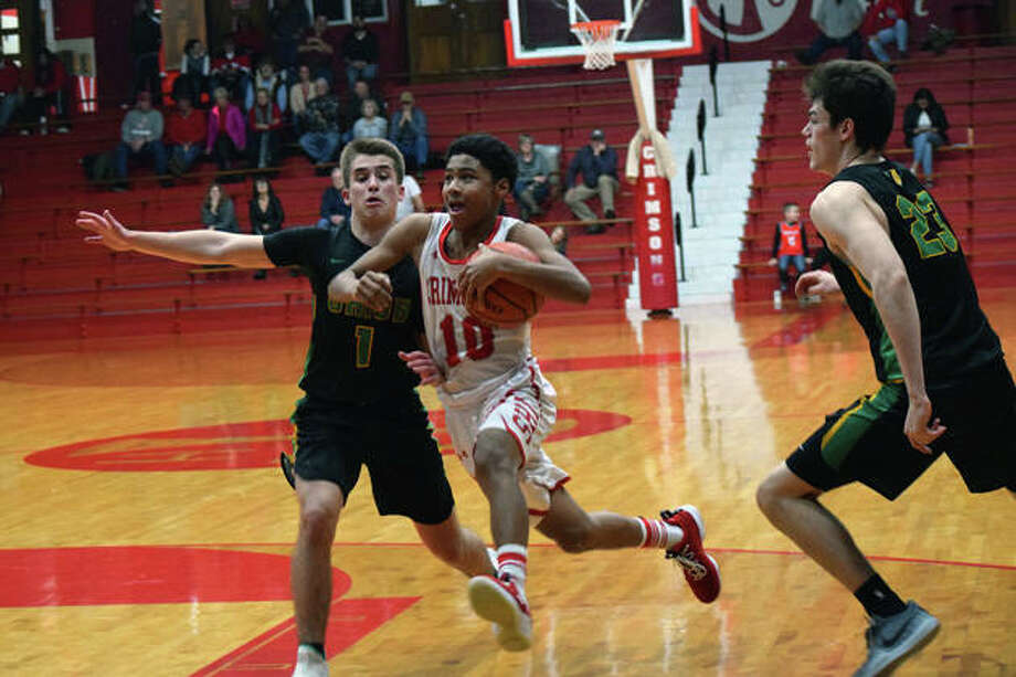 Jacksonville's Travell Pearson moves down the court Friday during a basketball game against U-High.