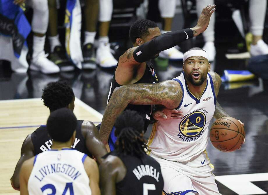 Warriors center DeMarcus Cousins drives to the basket while Clippers forward Mike Scott defends in the second quarter. Cousins scored 14 points in 15 minutes. Photo: Kelvin Kuo / Special To The Chronicle / online_yes