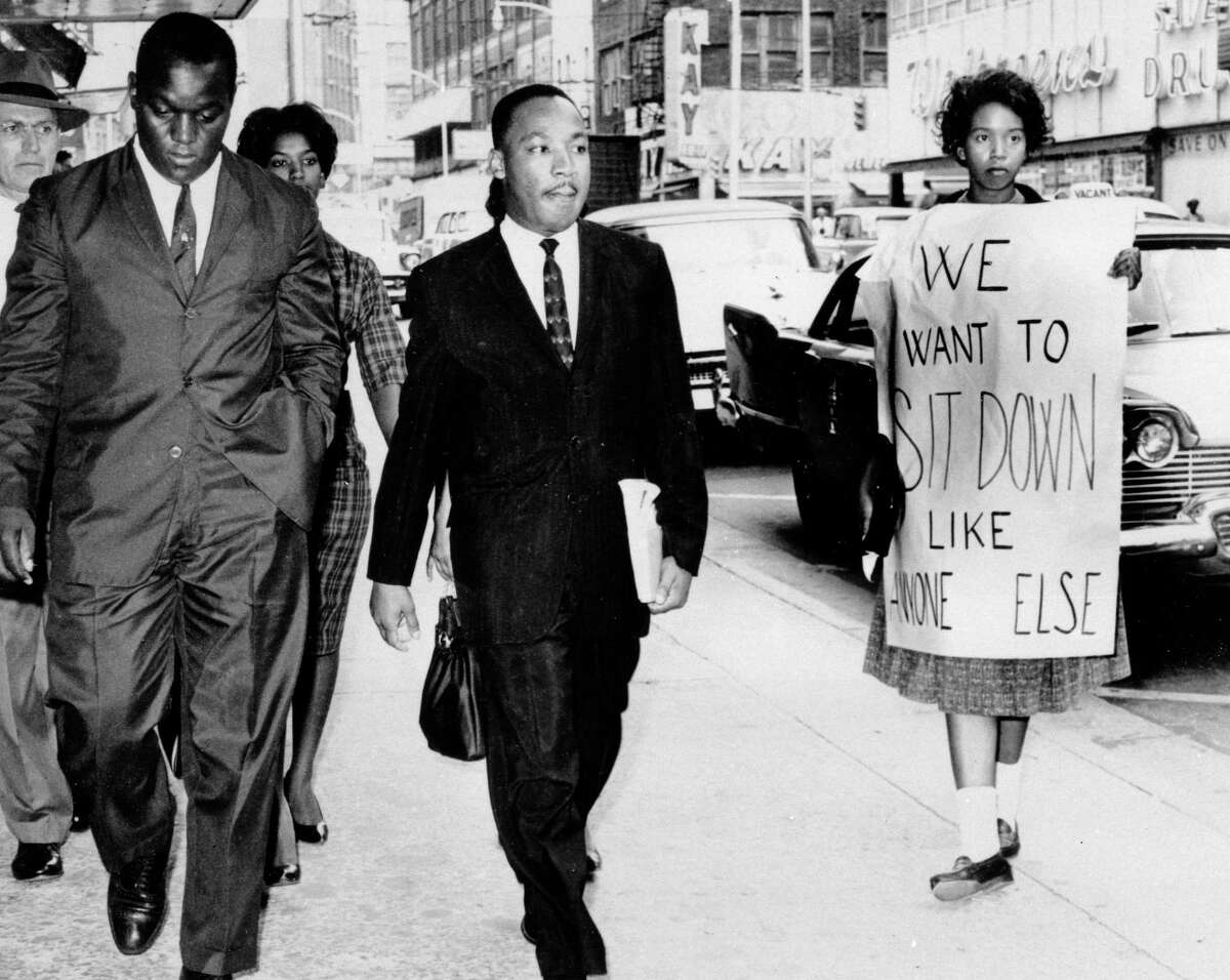 Dr. Martin Luther King Jr., under arrest by Atlanta Police Captain R.E. Little, left rear, passes through a picket line in front of a downtown department store on Oct. 9, 1960. With King is another demonstration leader, Lonnie King and an unidentified woman. The integration leader was among the 48 African-Americans arrested following demonstrations at several department and variety stores protesting lunch counter segregation.