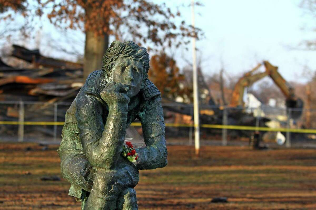 Flowers were left as a memorial on a nearby statue as clean-up continues after a fire destroyed the old theater at American Shakespeare State Park in Stratford, Conn. on Tuesday Jan. 15, 2019. Though the circumstances of the blaze have led many to speculate on its cause, Fire Marshal Brian Lampart said investigators have no evidence of arson at the property - though he cautioned the investigation is also in its early stages.