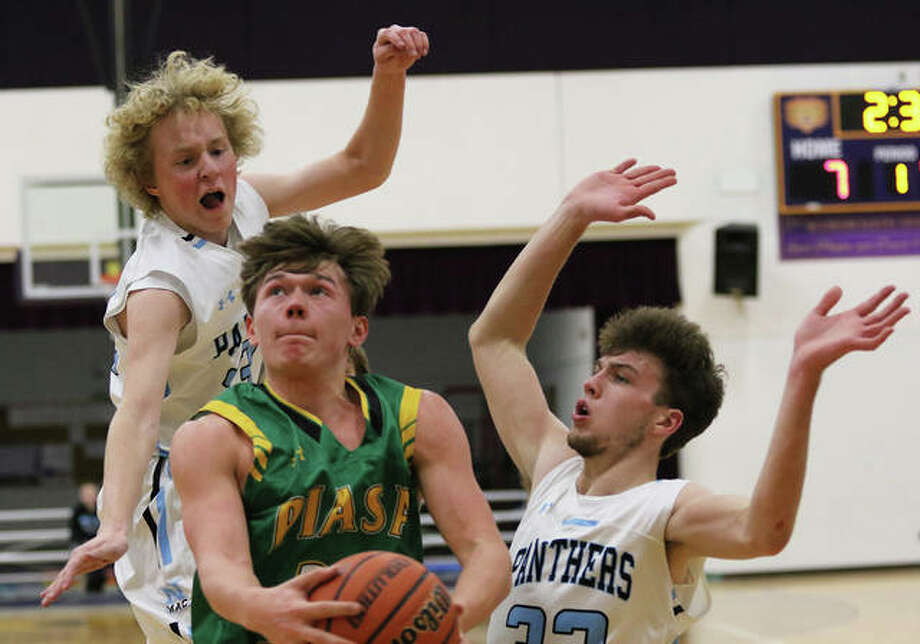 Southwestern's E.J. Kahl splits North Mac defenders Sam Mount (right) and Will Downs (left) to put up a shot in the lane Friday night in the championship game of the Macoupin County Tournament in Mount Olive. Photo: Greg Shashack / The Telegraph