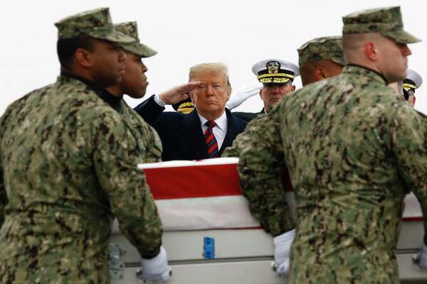 President Donald Trump salutes as a U.S. Navy carry team moves a transfer case containing the remains of Scott A. Wirtz, Saturday, Jan. 19, 2019, at Dover Air Force Base, Del. According to the Department of Defense, Wirtz, a civilian and former Navy SEAL from St. Louis, Mo., was killed Jan. 16, 2019, in a suicide bomb attack in Manbij, Syria.