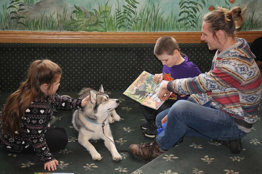 Kids got a chance to read to friendly Siberian Husky Akuna, Saturday, at the Bad Axe Library. Photo: Seth Stapleton
