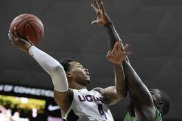 UConn's Jalen Adams (4) goes up to the basket as Tulane's Jordan Cornish defends on Saturday.