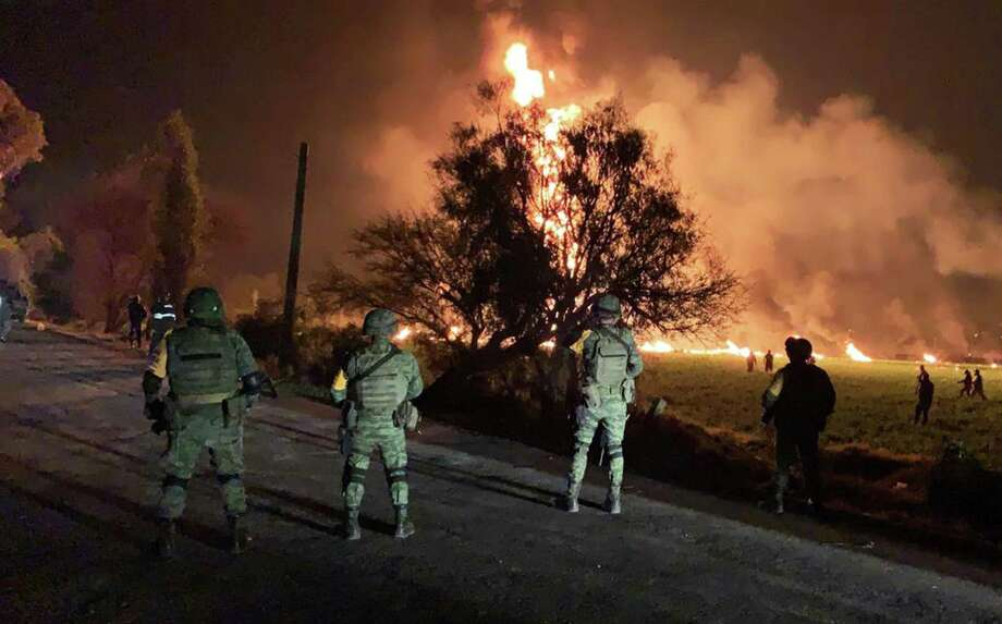 "TOPSHOT - This handout photo distributed by the Mexican Secretary of National Defence (Secretaria de Defensa Nacional) shows Mexican soldiers standing guard near a fire after a leaking gas pipeline triggered a blaze in Tlahuelilpan, Hidalgo state, on January 18, 2019. - A leaking fuel pipeline triggered a massive blaze in central Mexico, killing at least 20 people and injuring another 54, officials said. Omar Fayad, governor of Hidalgo state, said locals at the site of the leak were scrambling to steal some of the leaking oil when at least 20 of them were burned to death. (Photo by Handout / SECRETARIA DE DEFENSA NACIONAL / AFP) / RESTRICTED TO EDITORIAL USE - MANDATORY CREDIT ""AFP PHOTO / SECRETARIA DE DEFENSA NACIONAL "" - NO MARKETING NO ADVERTISING CAMPAIGNS - DISTRIBUTED AS A SERVICE TO CLIENTSHANDOUT/AFP/Getty Images Photo: Handout / AFP / Getty Images / AFP or licensors"