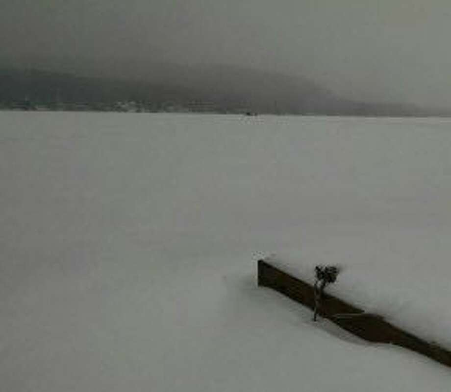 Ice fishermen are seen in the distance on Great Sacandaga Lake. Officials are urging caution to snowmobilers because of ice and marine hazards. Photo: Times Union