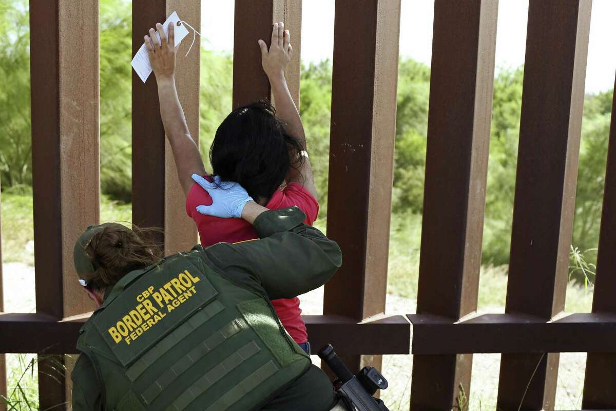 U.S Border Patrol Agent Amber Peterson pats-down Santos Abel Madriges, 34, from El Salvador, in Hidalgo County near McAllen, Texas, Thursday, July 19, 2018. Madriges was traveling with her 17-year-old son and together with a group of seven immigrants from Central America, turned themselves into authorities after illegally crossing the Rio Grande into the U.S.