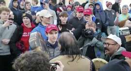 "In this Friday, Jan. 18, 2019 image made from video provided by the Survival Media Agency, a teenager wearing a ""Make America Great Again"" hat, center left, stands in front of an elderly Native American singing and playing a drum in Washington. The Roman Catholic Diocese of Covington in Kentucky is looking into this and other videos that show youths, possibly from the diocese's all-male Covington Catholic High School, mocking Native Americans at a rally in Washington. (Survival Media Agency via AP)"
