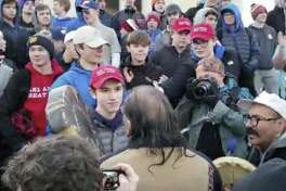 """In this Friday, Jan. 18, 2019 image made from video provided by the Survival Media Agency, a teenager wearing a """"Make America Great Again"""" hat, center left, stands in front of an elderly Native American singing and playing a drum in Washington. The Roman Catholic Diocese of Covington in Kentucky is looking into this and other videos that show youths, possibly from the diocese's all-male Covington Catholic High School, mocking Native Americans at a rally in Washington. (Survival Media Agency via AP)"""