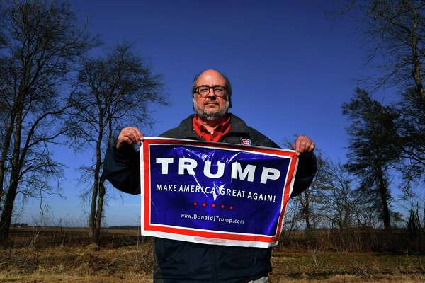 Joe Davidson, in Merigold, Mississippi, holds up one of the banners in support of President Donald Trump that he keeps in his car trunk.