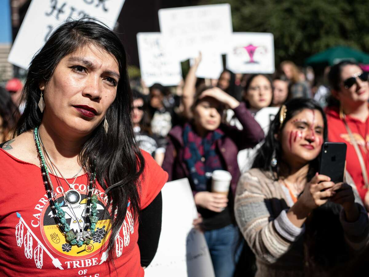 Attendees of the Women's March hold signs during rally on Saturday, January 19, 2019 held in front of the San Fernando Cathedral in downtown San Antonio, Texas.