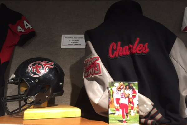 Memorial Titan legend and NFL running back Jamaal Charles' letterman jacket and high school helmet stand on display at the Museum of the Gulf Coast's Hometown Heroes exhibit, which opened Saturday.
