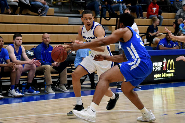 Wayland Baptist junior guard JJ Culver tries to drive past John Brown junior forward Quintin Bailey during a Sooner Athletic Conference men's basketball game on Saturday at Hutcherson Center in Plainview. Though Culver surpassed 1,000 career points, the Pioneers lost to the Golden Eagles, 73-72.