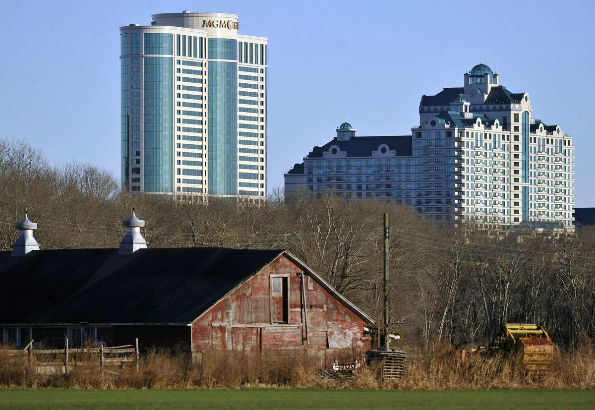In this Nov. 11, 2012 file photo, Foxwoods Resorts Casino and MGM Grand at Foxwoods buildings loom behind a barn in Mashantucket, Conn. Once one of America?•s wealthiest communities, the Mashantucket Pequot Indian reservation revived by the resort casino is reeling from a financial reversal that began in 2010. (AP Photo/Jessica Hill)