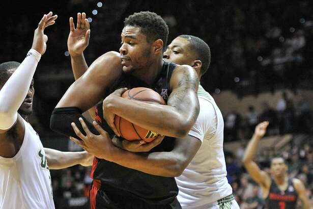 Houston forward Braeon Brady, center, protects the ball under pressure from South Florida's Laquincy Jareau, left, and Michael Door, right, during the first half of a NCAA college basketball game Saturday, Jan. 19, 2019 in Tampa, Fla. Houston defeated South Florida 69-60. (AP Photo/Steve Nesius)