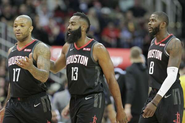 Houston Rockets forward PJ Tucker (17) talks to teammate James Harden (13) as they make their way to the bench with James Ennis III (8) during a time out on Saturday, Jan. 19, 2019 in Houston.