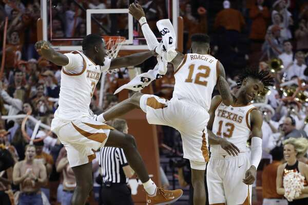 Texas guard Courtney Ramey (3), guard Kerwin Roach II (12) and guard Jase Febres (13) celebrate their win over Oklahoma in an NCAA college basketball game in Austin, Texas, Saturday, Jan. 19, 2019. Texas won 75-72. (AP Photo/Eric Gay)