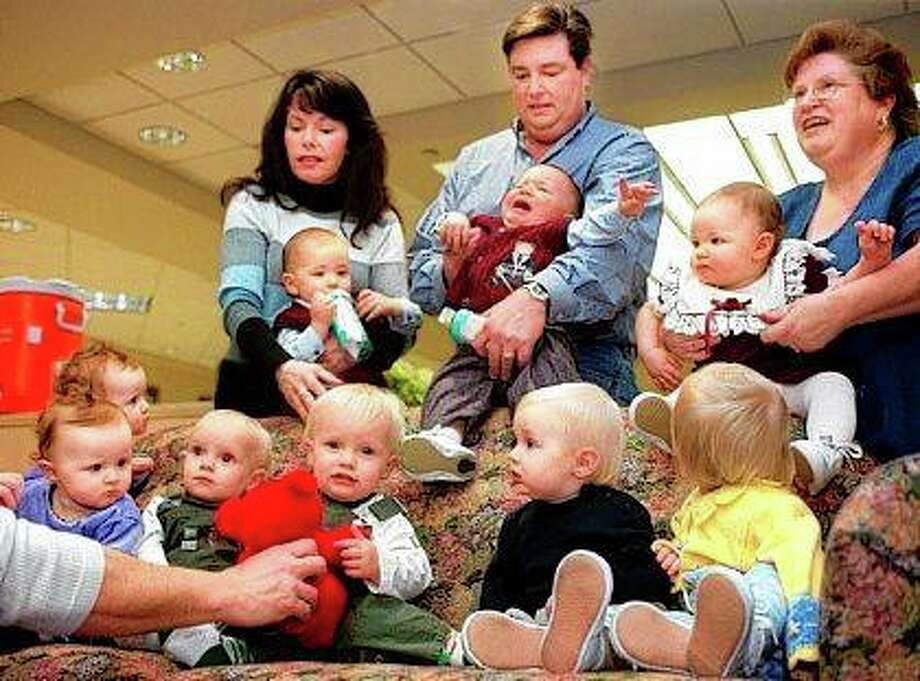 Darrin Dohme (center) has his hands full with son Dylan as wife Julle (left) holds Jacob and their triplets' godmother, Tena Fowler (right), holds Caroline during a first-anniversary reunion of the 'Magnificent Nine' — three sets of twins and a set of triplets all born in the same 24-hour period on Jan. 9-10, 2001, at Carle Foundation Hospital in Urbana. Joining them on the couch are twin sisters Mariya (from left) and Taelyn Harris of Georgetown; twin brothers David and Daniel Ekstam of Champaign; and Quinn Gard and his twin sister, Carrigan, of Danville. Photo: Heather Coit | The News-Gazette (AP)